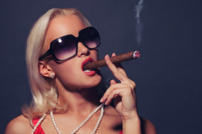 Blond woman in suglasses smoking cigar. Isolated on grey