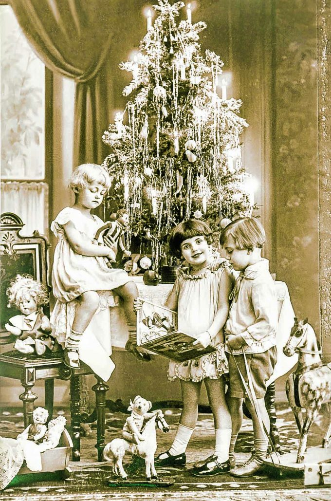happy kids with christmas tree, gifts and vintage toys. antique sepia picture with original film grain
