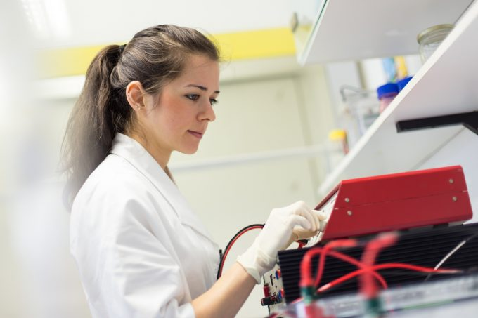 Focused attractive young life science researcher setting voltege on power supply to run electrophoresis for protein or DNA sepparation. Focus on the researcher's face.