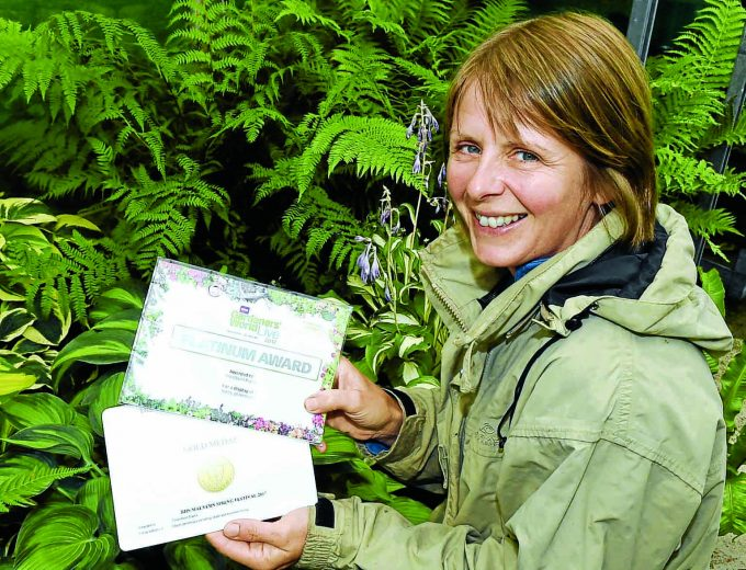 er *** Local Caption ***  PLANTING . . . Helen is pictured with her awards as she tends to her plants