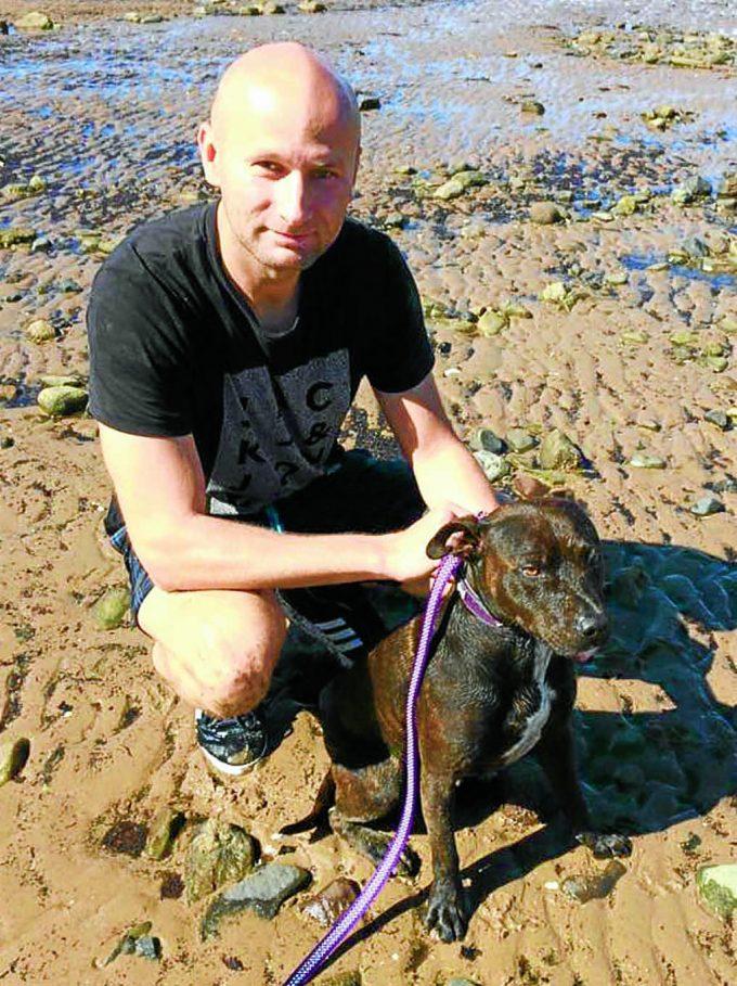 SELFLESS ACT . . . Blazej Reczko, manager of the Steamboat Inn, with Kia the Staffordshire Bull Terrier who he saved from drowning