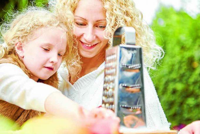 Mutter hilft Tochter beim Apfel reiben