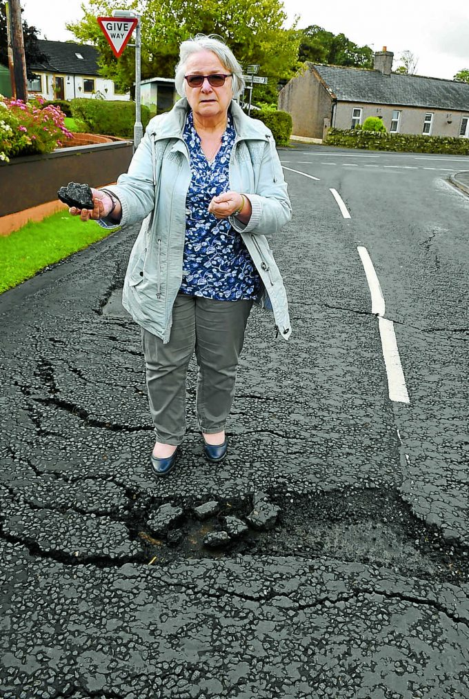 eaglesfield road cn *** Local Caption ***  SLIP AND SLIDE . . . Eaglesfield community councillor Elaine Irving inspects the cracked road