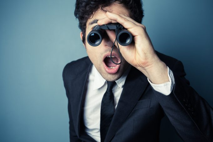 Young businessman is looking through binoculars and is surprised at what he sees