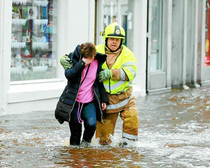 RESCUED . . . a firefighter helps a resident to safety during yesterday's flooding at Newton Stewart *** Local Caption *** RESCUED . . . a firefighter helps a resident to safety at Newton Stewart